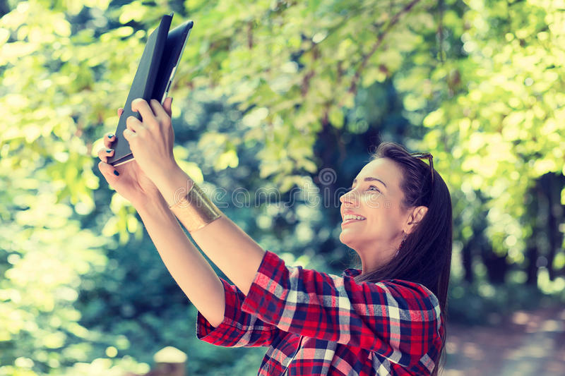 Girl using digital tablet taking picture of herself. stock image