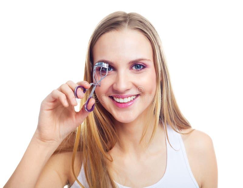 Girl using an eyelash curler. Pretty young blond woman using an eyelash curler stock image