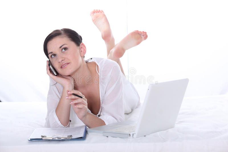 Girl using her laptop. Young pretty girl phoning and using her laptop stock photos