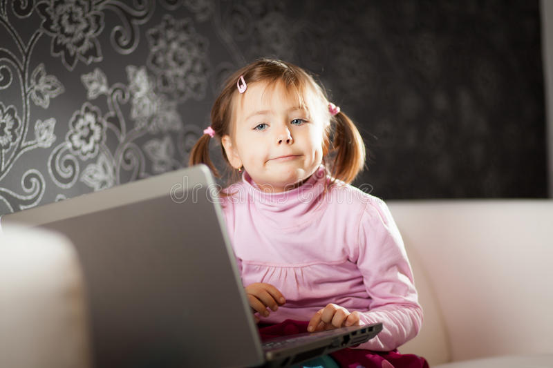 Girl using laptop. Young girl uses a laptop computer at home stock photo
