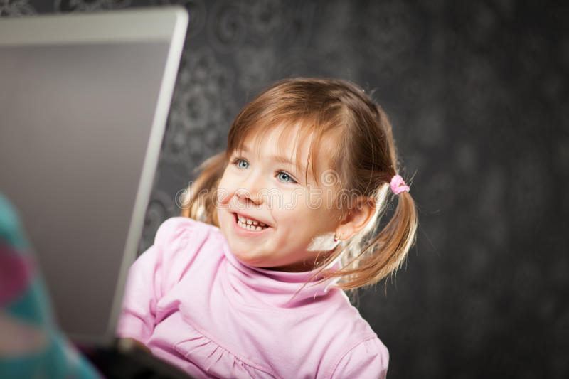 Girl using laptop. Young girl uses a laptop computer at home royalty free stock image