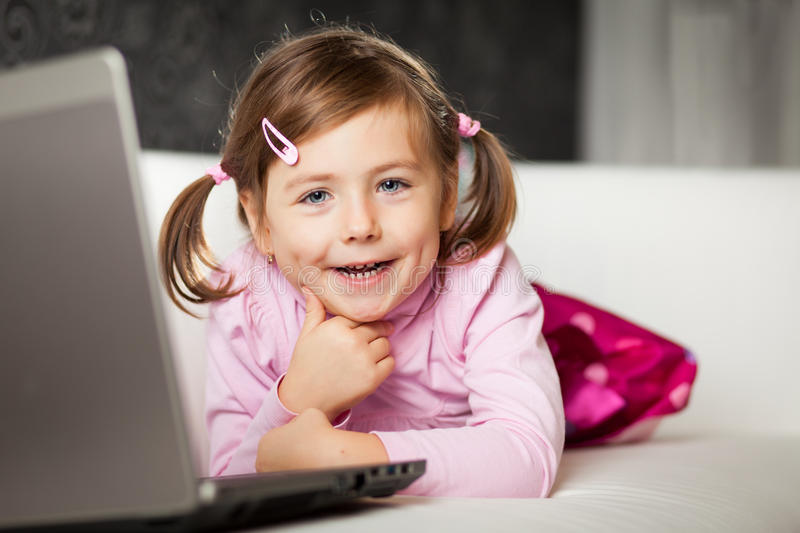 Girl using laptop. Young girl uses a laptop computer at home stock image