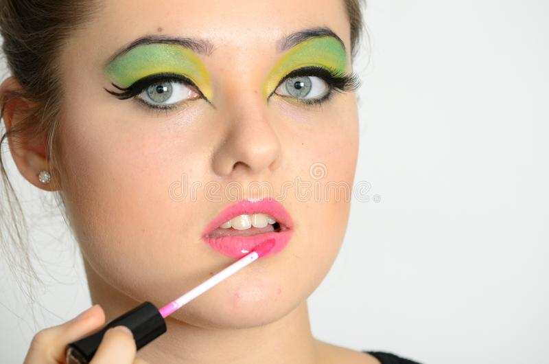 Girl using lip gloss. Portrait of young Polish female. Teenage girl with colorful makeup using lip gloss on her lips royalty free stock photo