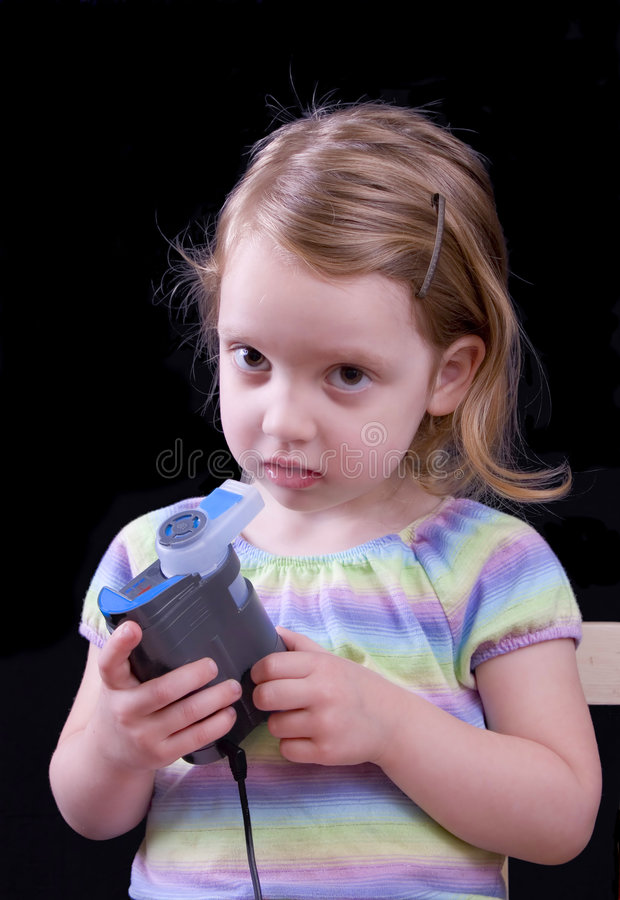 Girl using nebulizer. Three year old girl using a nebulizer to deliver a breathing treatment royalty free stock photo