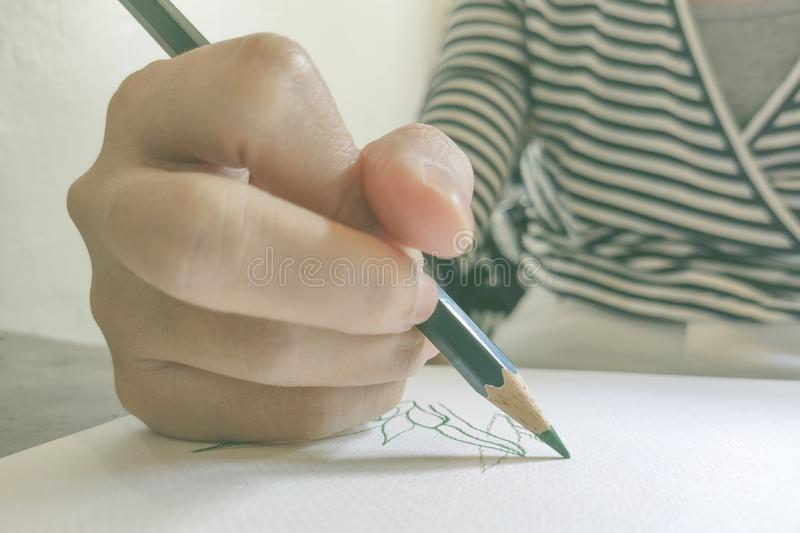A girl using pencil colors drawing something on white paper royalty free stock photos