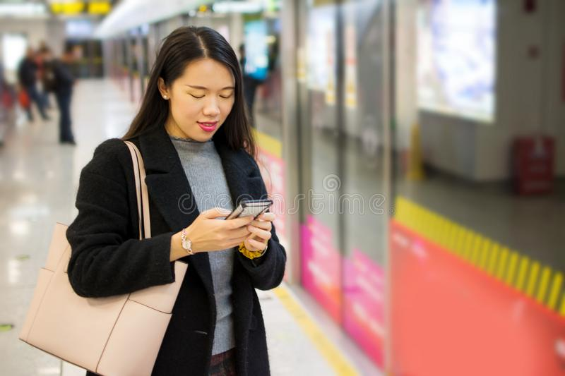 Girl using phone while waiting for the metro royalty free stock photo