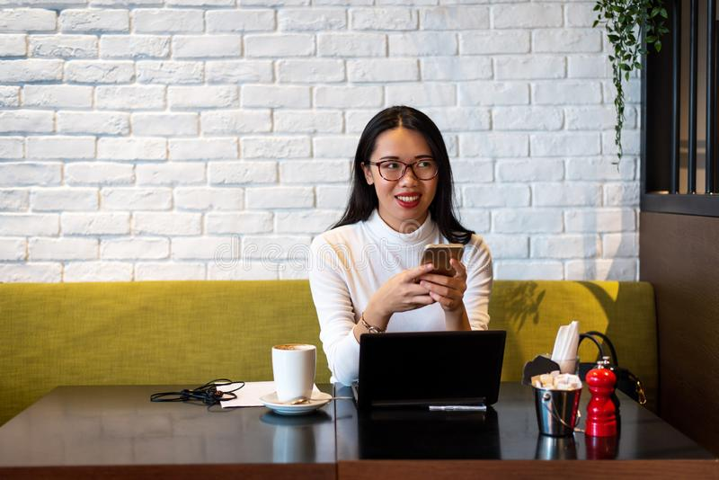 Girl using phone and working in a coffee bar royalty free stock photo