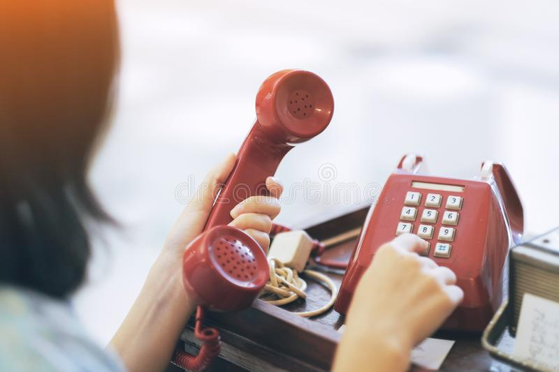A girl using the red vintage telephone royalty free stock photos