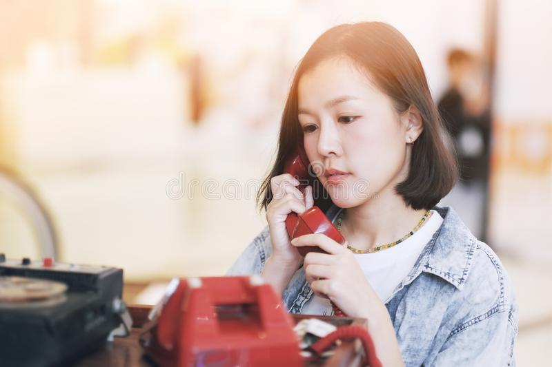 A girl using the red vintage telephone stock photos