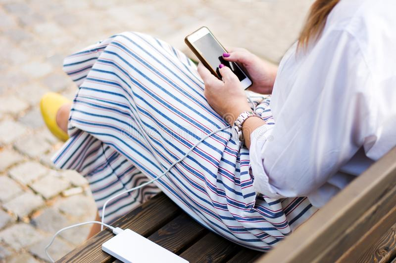 Girl using phone while charging on the power bank royalty free stock photography