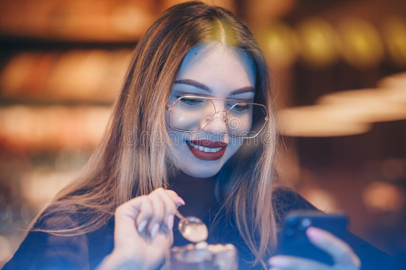 Girl Using Smartphone in Cafe Texting Sharing Messages on Social Media Enjoying Mobile Technology Relaxing in Coffee stock images