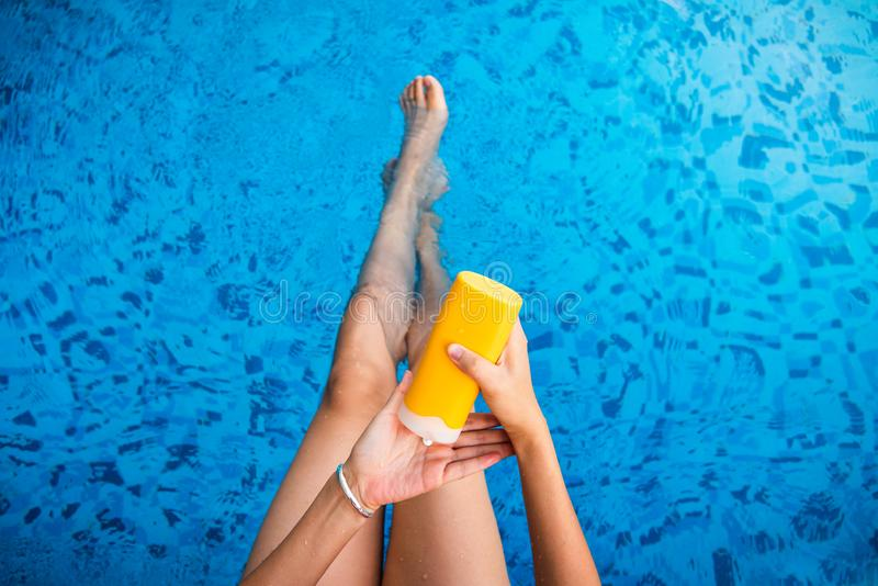 Girl using sun lotion at the pool. Girl using sun lotion at the swimming pool, applying, woman, summer, vacation, water, top, pov, first, person, suncream royalty free stock images