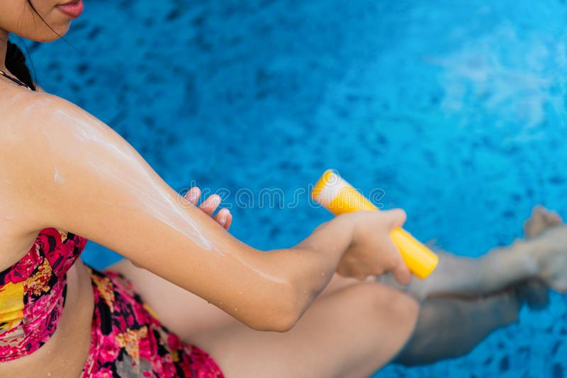 Girl using sun lotion at the pool. Girl using sun lotion at the swimming pool, woman, summer, vacation, water, top, applying, suncream, sunscreen, sunblock stock images