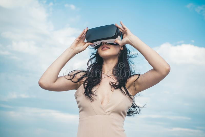 Girl using VR headset. Woman getting experience using VR-headset glasses. Visual reality concept. Digital future and stock images