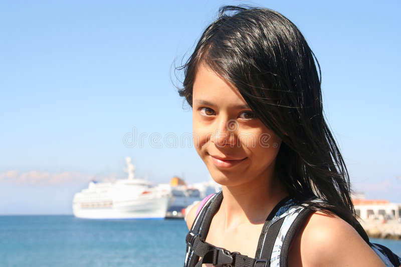 Girl on Vacation. Girl with passenger ship in the background royalty free stock image