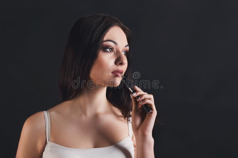 Young woman vaping e-cigarette on black. Girl with vape at black studio background closeup. Young woman smoking e-cigarette to quit tobacco. Nicotine free stock images