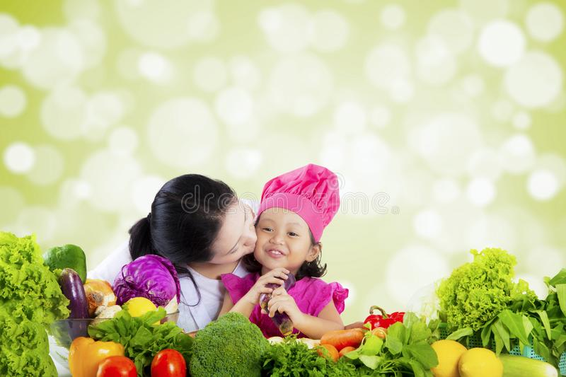 Girl with vegetables kissed by mother stock images