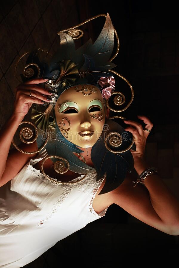 Girl in a venetian mask on a dark background.  royalty free stock image