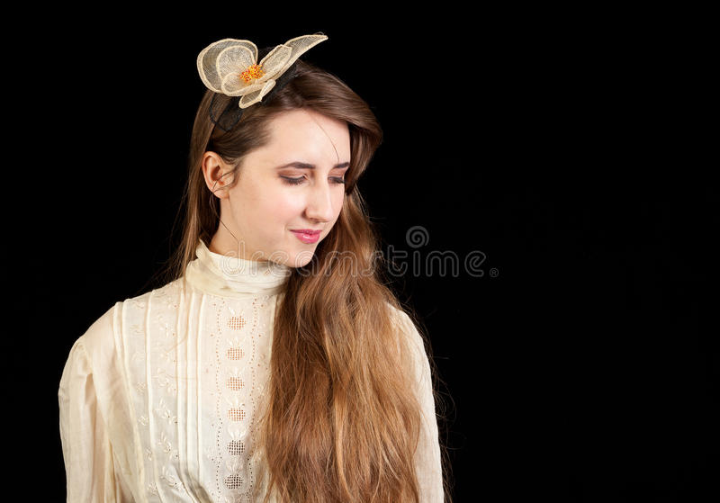 Girl in Victorian dress with hair piece. Looking down on a black background stock images