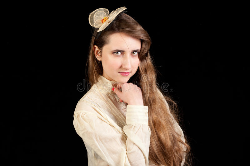 Girl in Victorian dress with hair piece. Playing with her hair and holding her hand under her chin on a black background royalty free stock photography