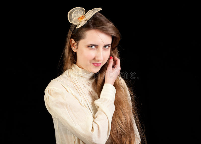 Girl in Victorian dress with hair piece. Playing with her hair and looking in the lens on a black background stock images