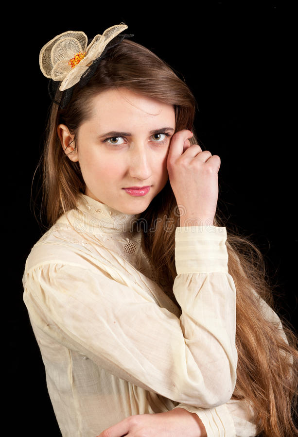 Girl in Victorian dress with hair piece. Playing with her hair and looking in the lens on a black background royalty free stock image