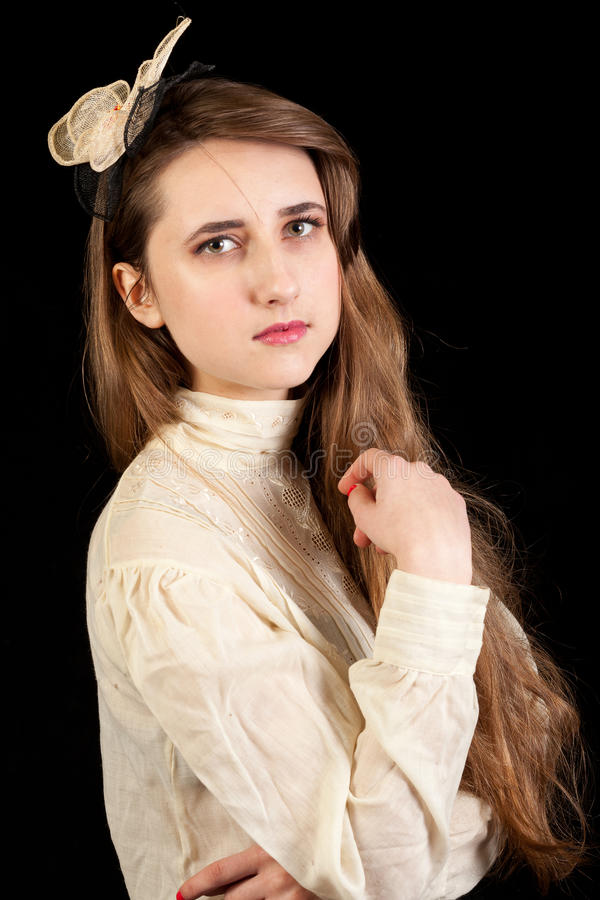 Girl in Victorian dress with hair piece. Playing with her hair and looking in the lens on a black background stock photography