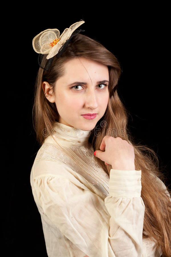 Girl in Victorian dress with hair piece. Playing with her hair and looking in the lens on a black background royalty free stock photo