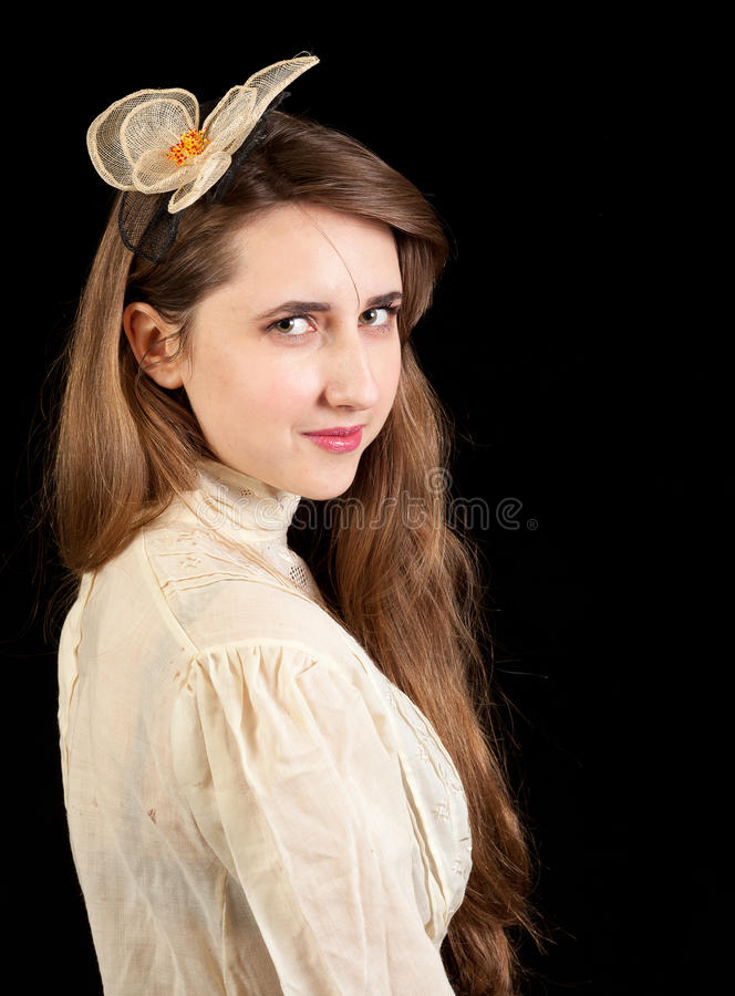Girl in Victorian dress with hair piece. In profile and looking in the lens on a black background royalty free stock image