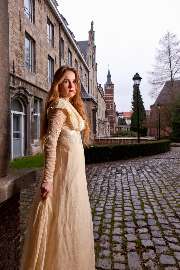 Girl in Victorian dress in a old city square royalty free stock photography