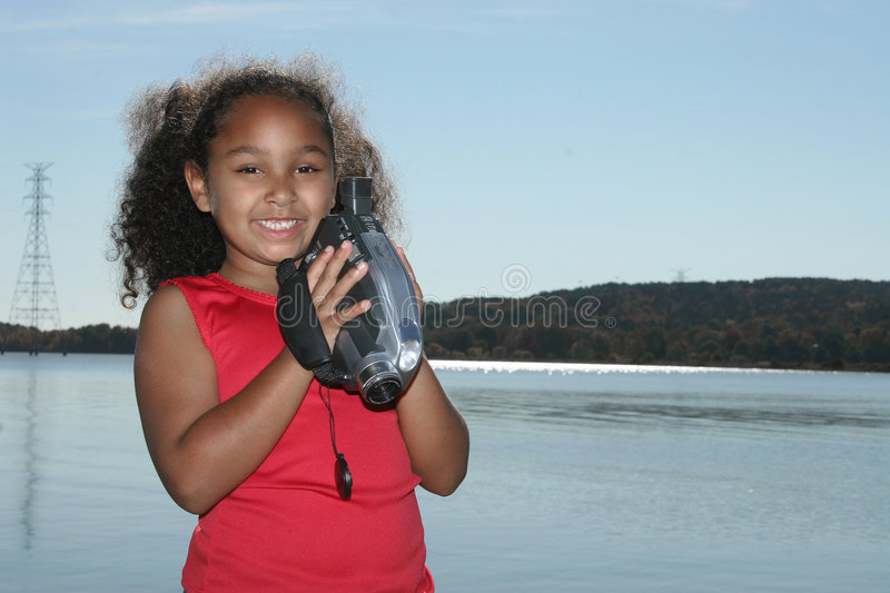 Girl with video camera. Cute African American girl standing in front of river holding video camera royalty free stock photo