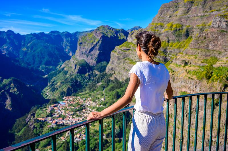 Girl at Viewpoint Eira do Serrado looking to Curral das Freiras village in the Nuns Valley in beautiful mountain scenery, royalty free stock photo