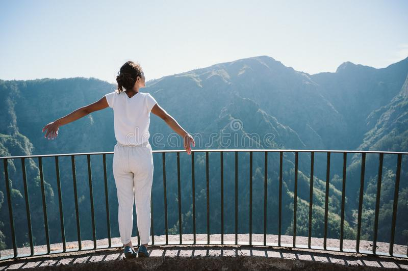 Girl at Viewpoint Eira do Serrado looking to Curral das Freiras village in the Nuns Valley in beautiful mountain scenery, royalty free stock image