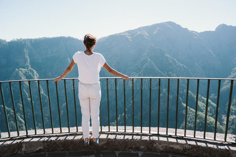 Girl at Viewpoint Eira do Serrado looking to Curral das Freiras village in the Nuns Valley in beautiful mountain scenery, stock images