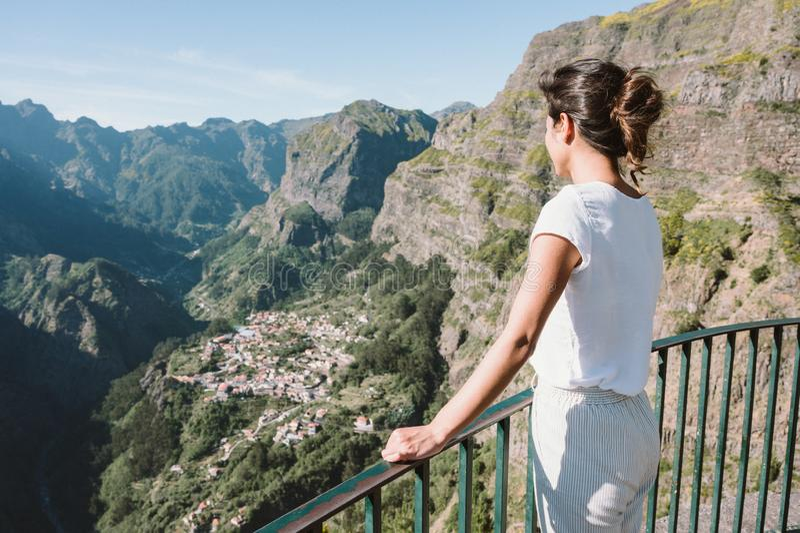 Girl at Viewpoint Eira do Serrado looking to Curral das Freiras village in the Nuns Valley in beautiful mountain scenery, royalty free stock photos