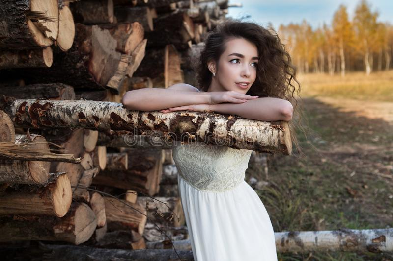 A young adult girl clapped on a birch log stock photo