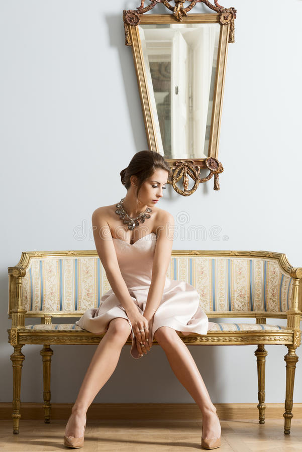 Girl in vintage aristocratic interior shot. Sensual brunette woman with elegant dress and classic hair-style sitting on vintage sofa in aristocratic room royalty free stock image
