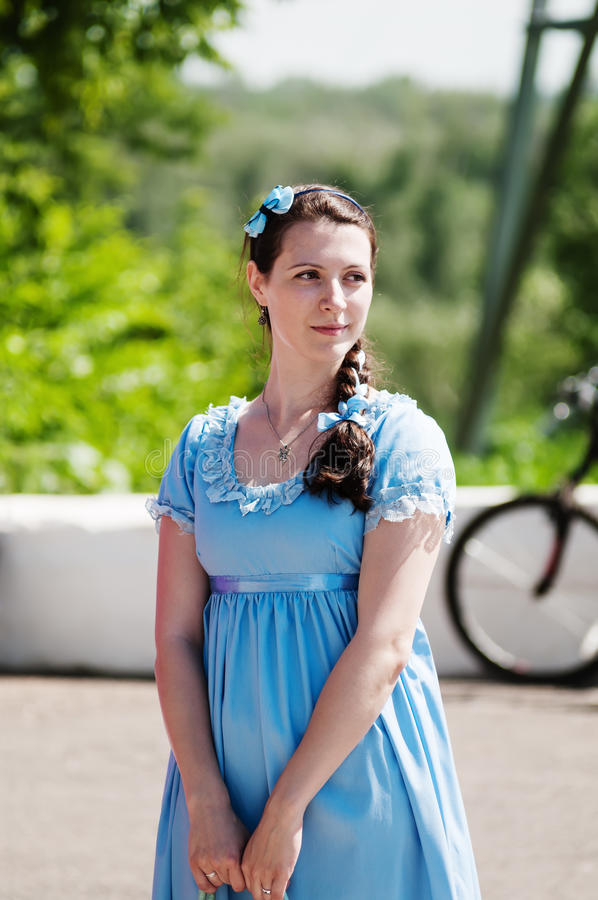 Girl in vintage blue dress on a city street stock photography
