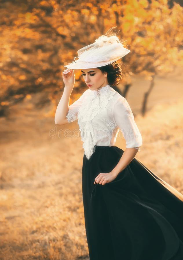 A girl in a vintage dress. Exquisite lady in a vintage dress in a beautiful hat walks among the hills, against the background of wild nature. Artistic stock photography