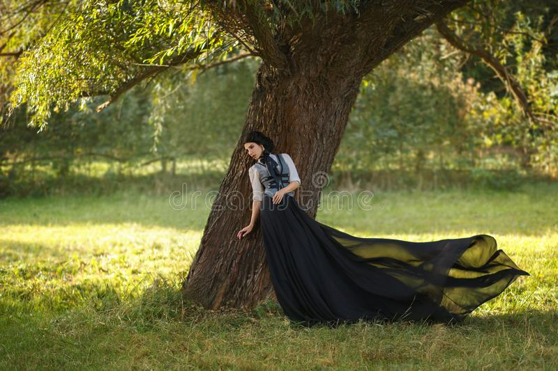 A girl in a vintage dress. Exquisite lady in a vintage dress for walking with a horse. A beautiful rider stands under a tree. Artistic Photography royalty free stock image