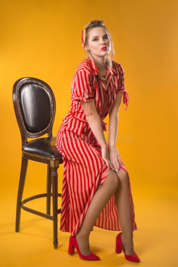 Girl in vintage style. In classic soft focus. Sits on a chair on a yellow background. In red striped royalty free stock photography