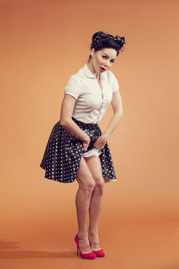 Girl in vintage style lifts skirt and shows pretty feet stock photography