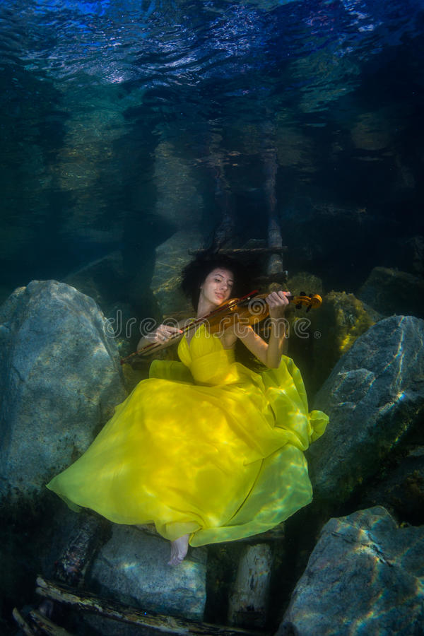 The girl with a violin under water stock photo