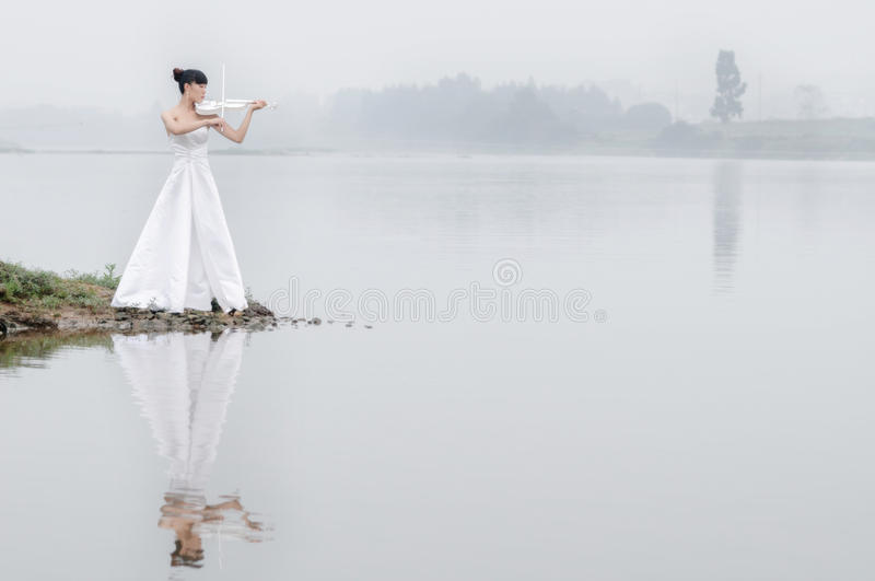 Girl and violin. A woman wearing a white dress standing in the misty morning river concentrate violin