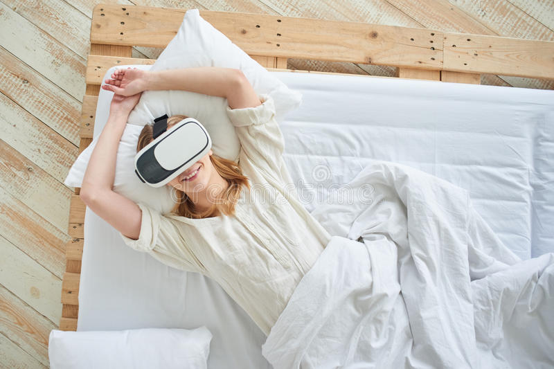 The girl in the virtual reality helmet. On the bed royalty free stock photo