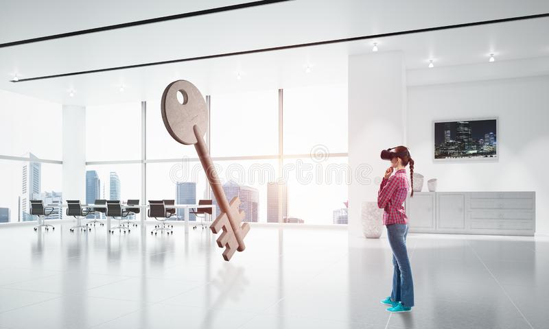 Girl in virtual reality mask experiencing virtual technology world. Mixed media. Young woman in virtual reality helmet looking at stone key symbol. Mixed media stock images