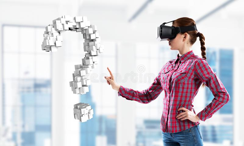 Girl in virtual reality mask experiencing virtual technology world. Mixed media stock photography