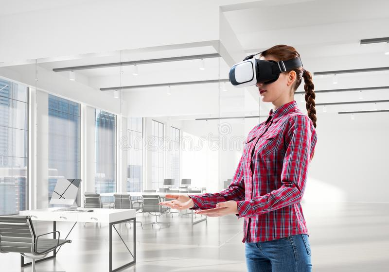 Girl in virtual reality mask experiencing virtual technology world. Mixed media stock photos