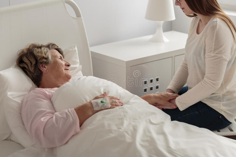 Girl visiting grandmother at hospital. Photo of caring girl visiting her ill grandmother at hospital stock photography