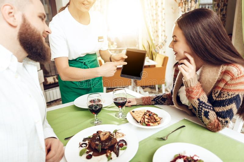 Girl waiter takes an order from a young couple stock photo